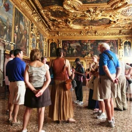 Gold adorned room in the Doges Palace with tour group in Venice