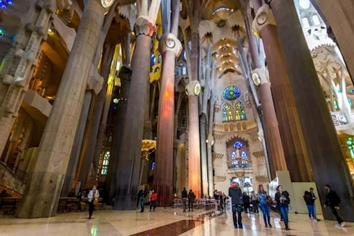 Sagrada Familia stunning interior being admired by tourists in Barcelona