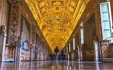 People walking through the Gallery of Maps at the Vatican Museums in Rome