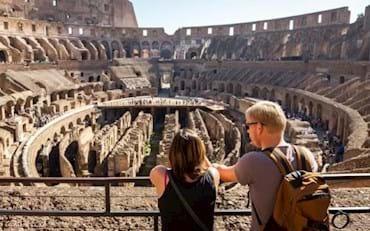 Turistas visitando el Coliseo en Roma y mirando los subterraneos