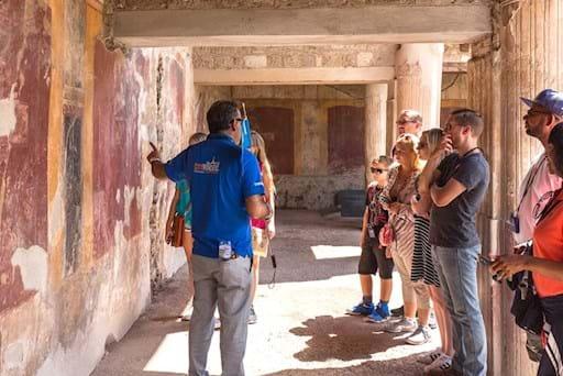Pompeii group tour admiring the frescoes at the ancient Pompeii houses