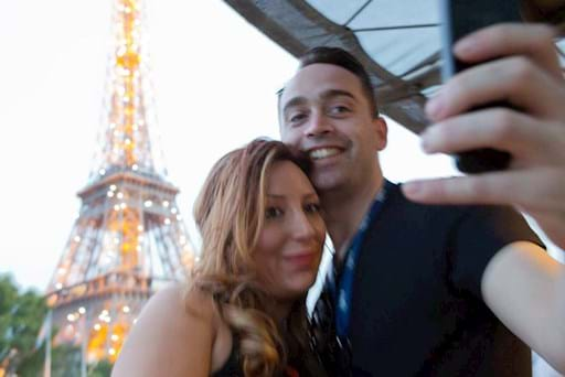 Couple taking a selfie in front of the Eiffel tower from a cruise