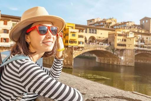 tourist admiring the Arno river in front Ponte Vecchio