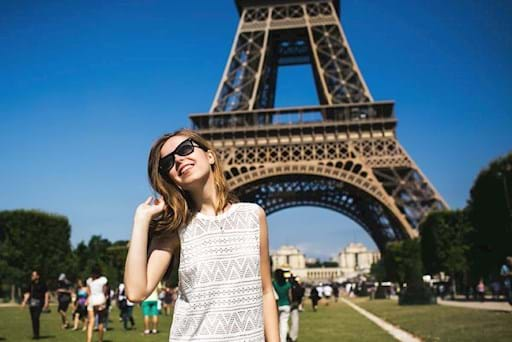 Beautiful girl taking a picture in front the Eiffel Tower