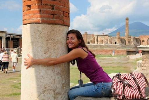 Tourist hugging an ancient column in Pompeii