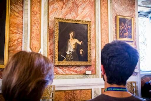 Couple looking at one of Caravaggio painting inside the Borghese Gallery