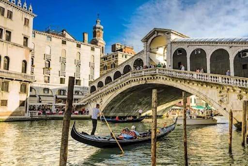 Gondola passing by the Rialto Bridge