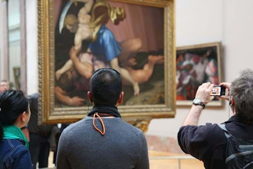 tourists taking a picture of a painting inside the louvre