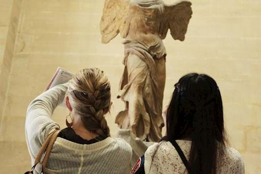 friend looking at a statue inside the louvre