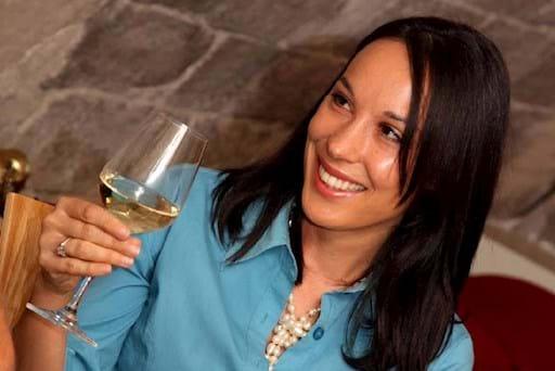 Beautiful girl tatsing some white wine
