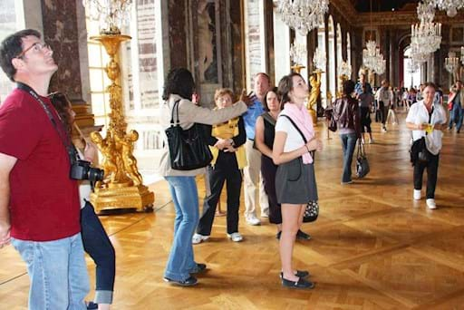 tourists admiring the versailles palace