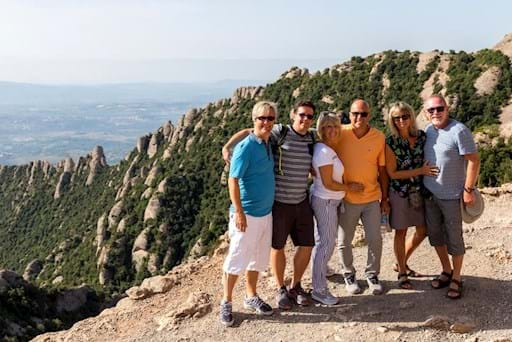 Group of tourists posing for a photo near a mountain edge in Montserrat