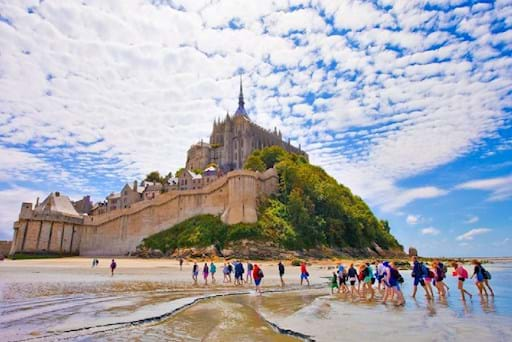 people walking along the beach of Mont Saint Michel