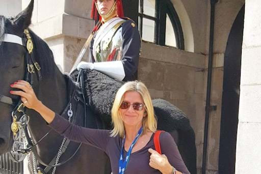 woman taking a picture with a guard on a hours in London
