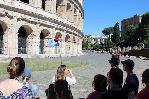 tour guide outside the colosseum talking to her group