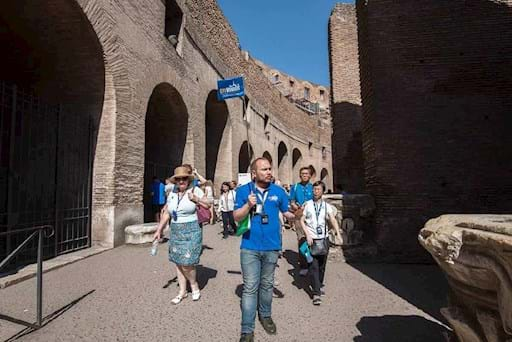 tour guide with tourists inside the colosseum