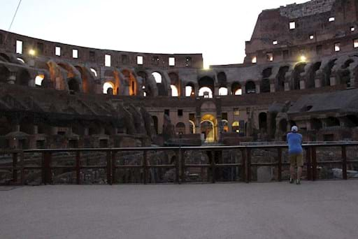tourist admiring the colosseum at sunset