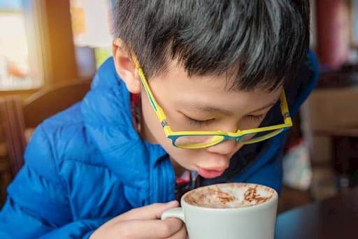 Young boy drinking hot chocolate
