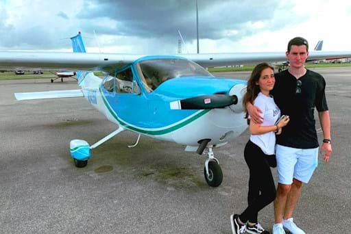 young couple posing in front of a plane