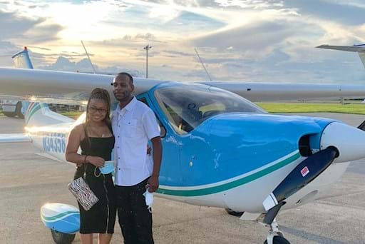 couple posing in front of a plane